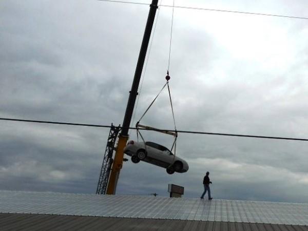 Polícia usou um guindaste para conseguir retirar o veículo do telhado (Foto: Benton Police Department)