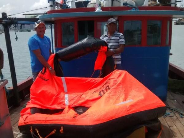 Nilton Pereira e um tripulante, do barco que resgatou o grupo em alto-mar, mostram balsa onde pescadores se apoiavam quando foram encontrados; equipamento furou no dia em que foram avistados (Foto: Lena Sena/G1)