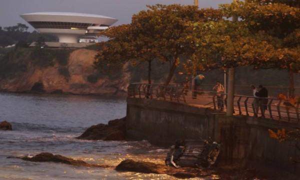 Carro invade calçada, derruba grade de proteção e despenca no mar no RJ