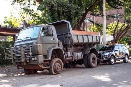 O caminhão tem marcas de disparos na porta, um vidro quebrado e um pneu furado.